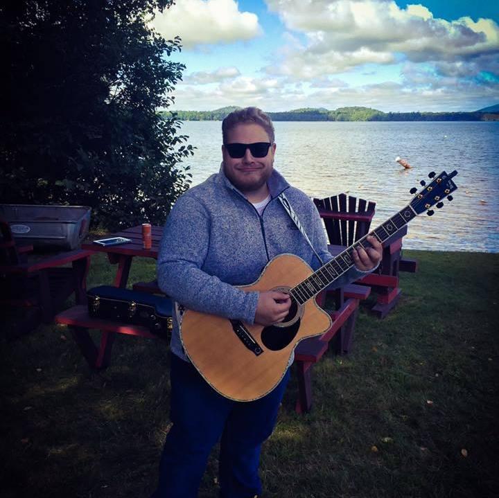 man playing guitar in front of lake